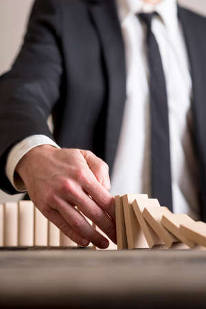 Vertical close-up of businessman wearing suit interrupting domino effect by stopping wooden dominoes bricks from crumbling with his hand. Standard-Bild