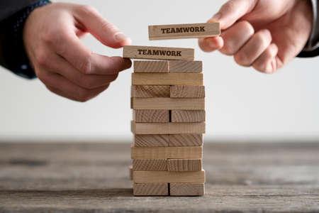 Deux mains mettent des dominos sur une pile de briques de bois avec des panneaux d'affaires en équipe sur la surface de la table rustique. Banque d'images - 72295998