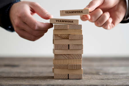 Two hands putting dominoes onto stack of wooden bricks with teamwork business signs on rustic table surface.