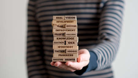 Close-up stretched hand holding stack of wooden bricks with motivational business signs, incognito man in stripped sweater blurred in background. Reklamní fotografie