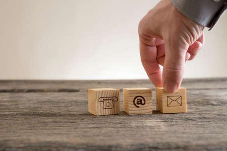 Würfel mit Kontakt Symbole - Umschlag, auf Zeichen und Telefon auf einem rustikalen Tisch von einem Geschäftsmann konzeptionellen der Kommunikation und Kundenbetreuung gelegt.