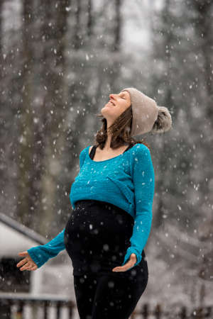 Pregnant woman in rolled up blue sweater and winter hat, standing outside in snowfall with arms spread and head thrown back, smiling enjoying weather. Stock Photo