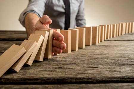 to interfere: Man stopping domino effect on wooden table. Business success concept. Copy space.