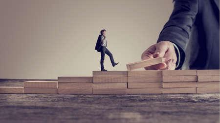 Image rétro vintage d'une personne d'affaires qui monte les marches, tandis que la main de l'autre homme construit des escaliers pour lui dans une image conceptuelle de la promotion, du leadership et de l'opportunité personnelle et professionnelle. Banque d'images - 73152780