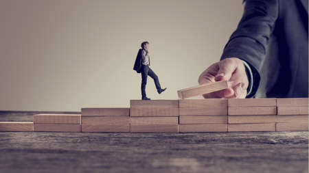 Retro vintage style image of a business person walking up steps, while the hand of other man building stairs for him in a conceptual image of personal and career promotion, leadership and opportunity.