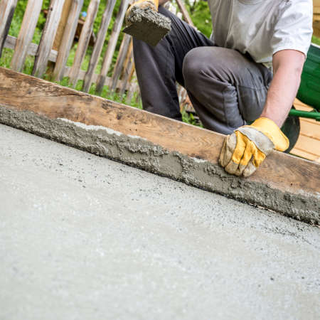 Hands of kneeling worker flattening freshly laid concrete outdoors with length of wood.