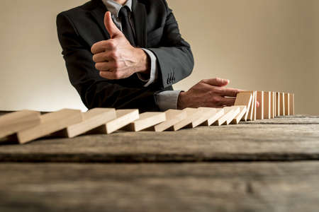 Close-up view of man in business clothes stopping dominoes row from crumbling and showing thumbs up gesture, on rough wooden table with copy space. Stock Photo