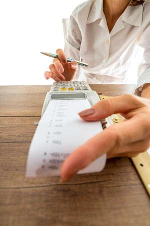 数字キーに指に過去のストリップの紙プリント アウト低角度のビューを持つマシンを追加する手動で彼女の会計をしている女性。