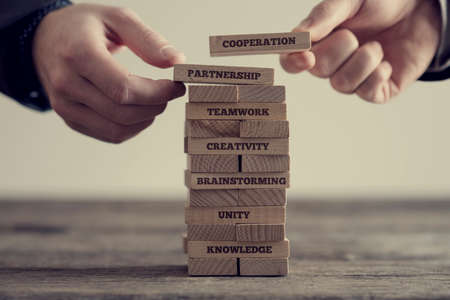 Close-up of hands putting dominoes onto stack of wooden bricks with motivational business signs on brown table surface, vintage effect toned image.