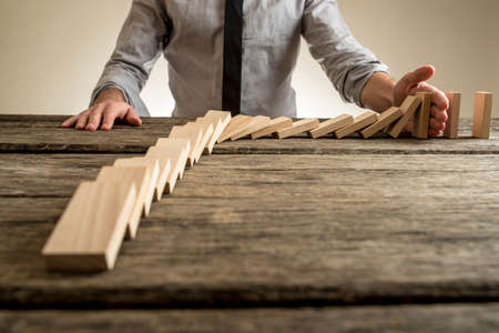 Businessman hand stopping domino effect. Rough wooden table with copy space.