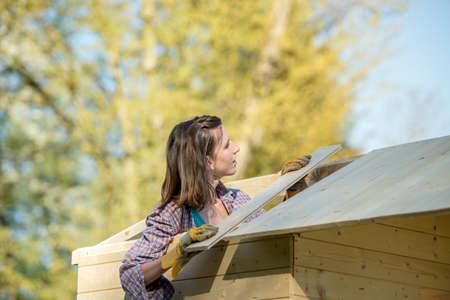 Junge Frau im Karohemd, das eine hölzerne Planke auf Dach der Gartenhalle (Hütte oder Summerhouse), ein Do-it-yourselfbau, Hintergrund von Bäumen setzt. Standard-Bild - 75712033