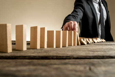 Businessman stopping domino effect with his finger. Business solutions concept.