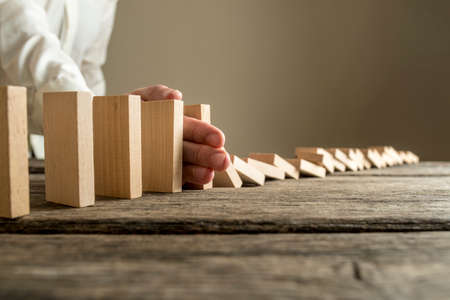 Man in white shirt stopping domino effect on wooden table. Business success concept. Archivio Fotografico
