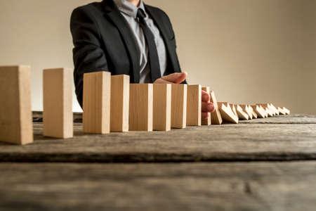Een zakenman die een pak draagt die naast een reeks verticale houten platen staat als zij elkaar vallen. Concept van domino-effect, waarbij één bedrijfsfout zorgt voor verdere ineenstorting.