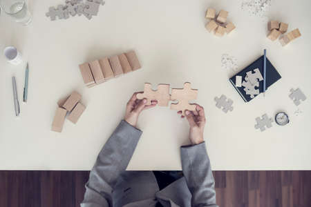 Top view of female hands assembling two wooden puzzle pieces with notebook, pen and other important metaphorical elements lying on white desk, toned retro effect.