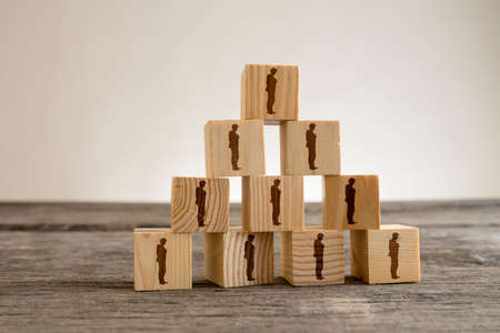 Leadership and human resources concept with wooden blocks with businessman silhouettes structured into a pyramid.