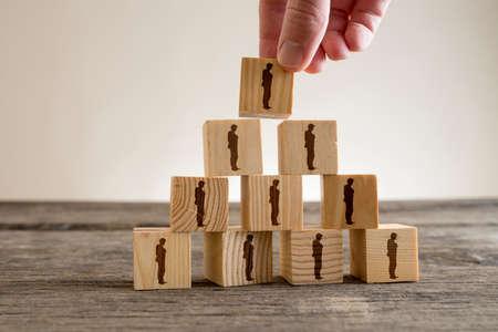 Mens die een toren van houtsneden met menselijke silhouetten, personeel en beheersconcept stapelt.
