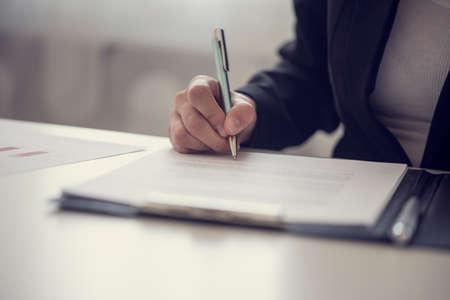 Retro vintage stijl beeld van een zakenvrouw ondertekenen van een contract of een document op een kaart. Stockfoto - 77110165