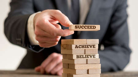 Businessman building tower of wooden domino bricks with motivational concept signs Believe, Achieve and Succeed.