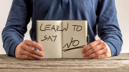 Front view of a man showing an open note pad with a handwritten message - Learn to say no.