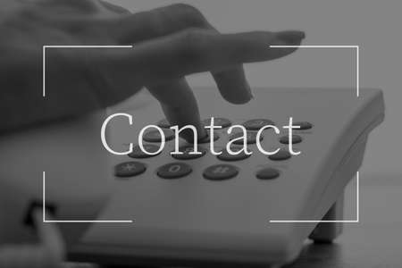 Contact text over female hand dialing a telephone number on white landline phone. Фото со стока