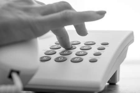Monochrome image of female hand dialing a telephone number on a white landline phone. Stock Photo
