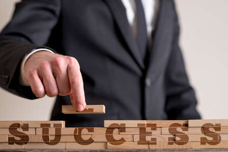 Businessman building a structure of wooden dominos while assembling word Success. Stock Photo