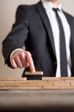 Businessman in business suit placing wooden blocks on table, conceptual of strategy and investment.
