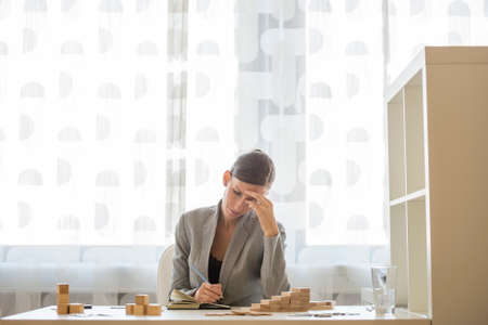 Businesswoman working at office desk writing on notepad beside stacks of wooden blocks on her desk looking a bit stressed.