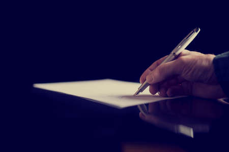 Businessman signing a document or taking notes, close up view of his hand and the paper, retro effect faded look.