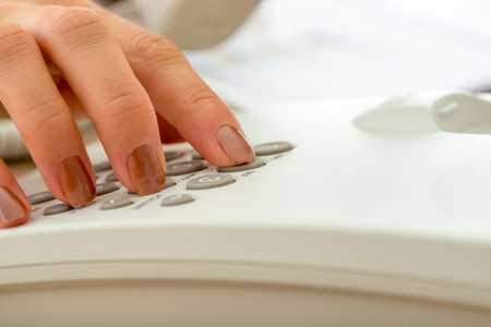 Closeup of female hand dialing a telephone number.