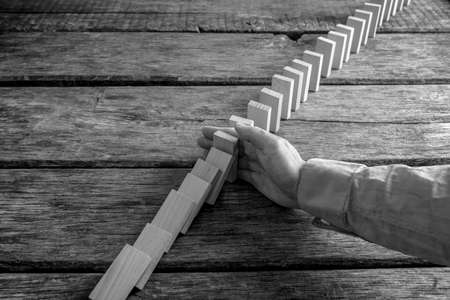 Monochrome image of a businessman preventing dominoes from crumbling with palm on wooden table. Stock Photo