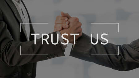 Trust us text over conceptual business scene with two partners gripping their hands. Stock Photo