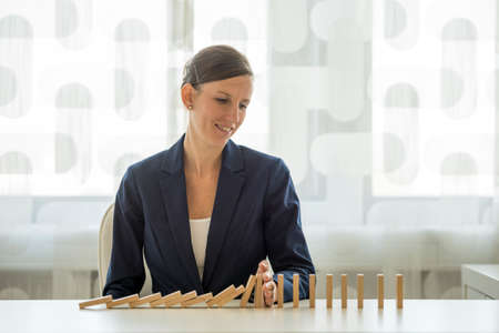 Businesswoman preventing dominoes from crumbling with palm on white wooden table. Stock Photo
