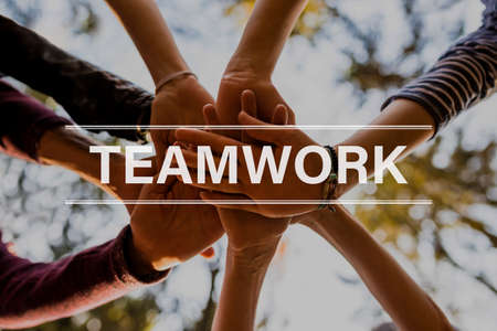 Teamwork text over four people stacking hands outside in nature. Stock Photo