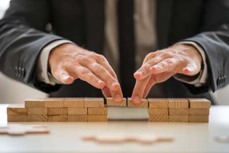 Businessman in suit assembling a bridge made from little blocks. Stock Photo