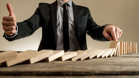 Businessman stopping dominoes row from crumbling and showing thumbs up gesture, on rough wooden table. Stock Photo