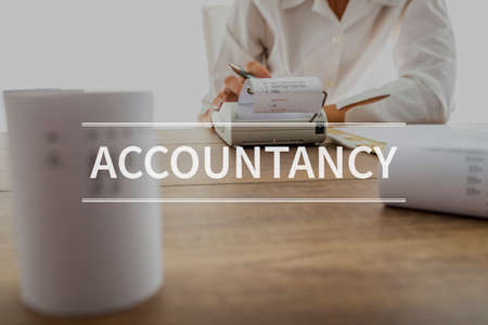Accountancy text over accountant or financial adviser making calculations using adding machine. Stock Photo