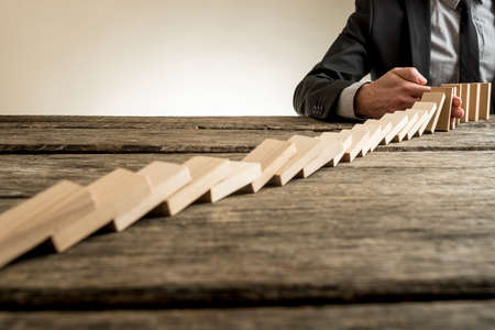 Businessman wearing suit interrupting domino effect by stopping wooden dominoes bricks from crumbling with his hand.
