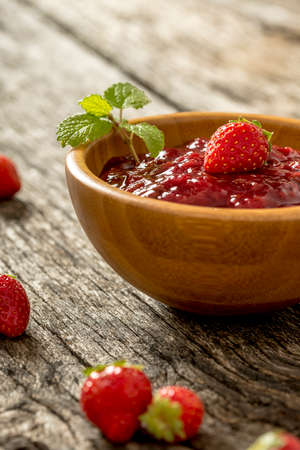 Wooden bowl full of strawberry marmalade with fresh ripe strawberries scattered around on wooden desk. 版權商用圖片