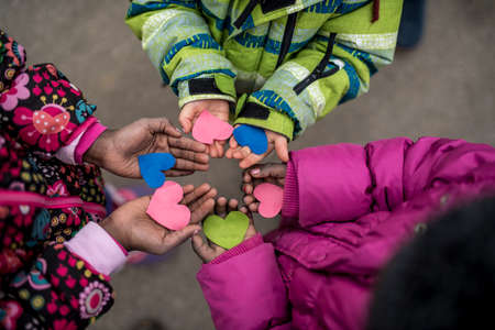 manos unidas: Children holding hearts cut of colored paper in their hands standing in circle symbolising love and friendship, view from above.