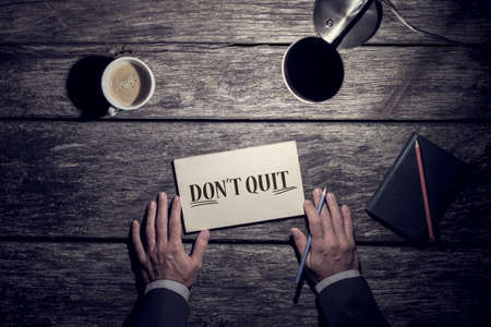 Motivational business concept - Dont Quit with underlined word Do It written on a card lying on a rustic wood desk with a mans hands holding a pen, lamp and mug of coffee viewed from above. Фото со стока