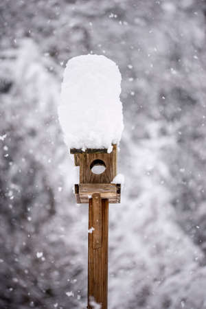 Wooden bird feeder with a tall cap of snow standing in a winter garden with snow-covered trees and falling snowflakes. Stock Photo