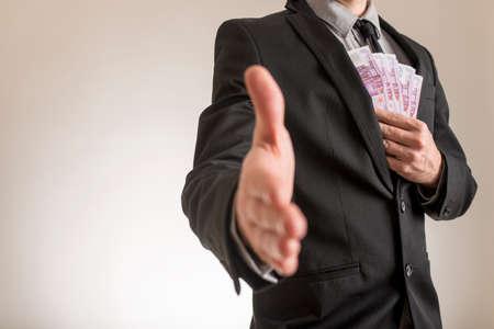 Businessman in elegant business suit offering his hand in handshake while holding several 500 euro bills near inside pocket of his jacket. Corruption or bribe concept. Banco de Imagens
