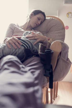 レトロな効果消えてし、トーンを彼女の足で彼女のひざに彼女の子供をあやしながらの日中室内で椅子で休んで女性のイメージ。 写真素材