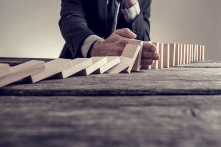 Retro effect faded and toned image of a businessman stopping domino effect on wooden table. Business solution concept. Stock Photo