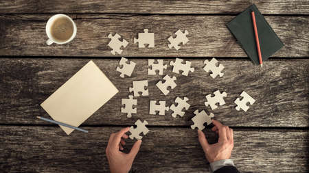 Retro style image of male hands in business suit trying to find a solution to a problem by arranging and matching puzzle pieces on a textured rustic wooden desk, top view.