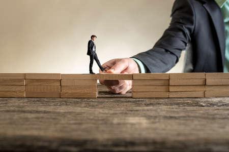 L'homme résolut des problèmes en construisant un pont avec un bloc en bois pour couvrir un espace pour un petit homme d'affaires marchant. Banque d'images - 81805858