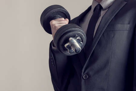 Retro effect faded and toned image of a businessman doing dumbbell biceps curl wearing a formal suit.