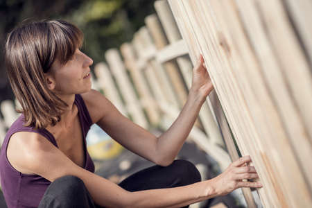 Retro effect faded and toned image of a woman building a garden fence in a close up side view of her kneeling. Stock Photo